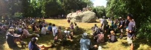 Large group of people surrounding a boulder.