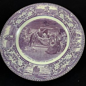 Blue and white dinner plate with Pilgrims depicted at center