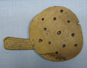 Wooden scoop with holes, handwritten message on handle.