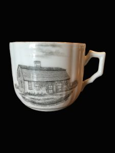 Tea cup with image of saltbox house in black and white