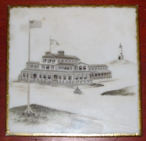 Ceramic tile with image of a large hotel and American flag at center. Monument in back.