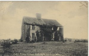 Black and white photograph of the John Alden House covered with ivy.
