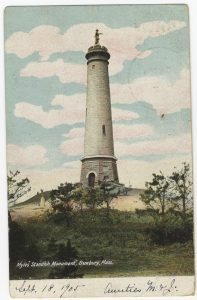 Color postcard of the Myles Standish Monument with writing at bottom.