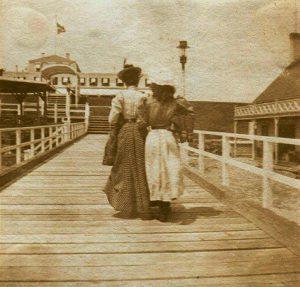 Two women in antique dresses with their backs to camera, on wooden walk, hotel in background.