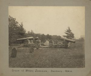 View of grave of Myles Standish with stone wall and cannons, tombstones in foreground.