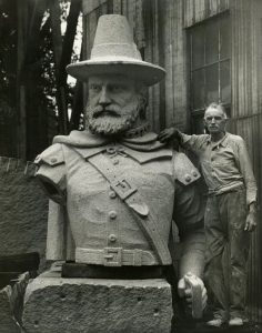 Large bust sculpture of Pilgrim Myles Standish with man standing next to it.