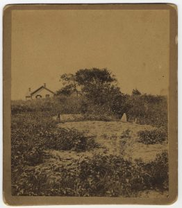 Image of field with bare spot, house in background. Site of Myles Standish's grave, Duxbury.
