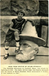 Small girl sitting next to sculpture head of Pilgrim Myles Standish with hat.
